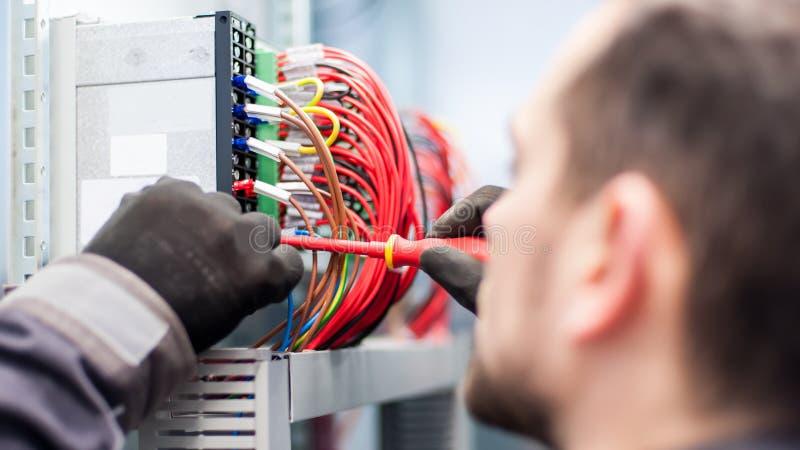 O close up do coordenador do eletricista trabalha com fios do cabo bonde fotografia de stock