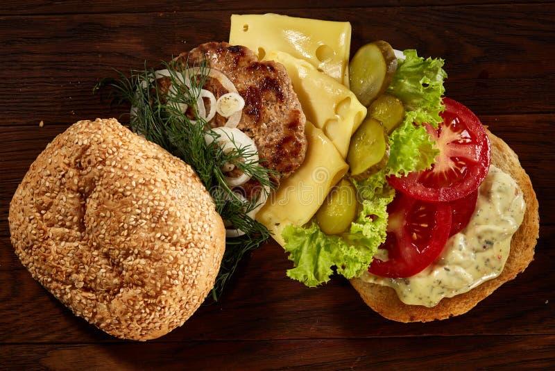 O close-up do hamburguer americano tradicional com queijo e hortaliças arranjou no fundo de madeira fotografia de stock