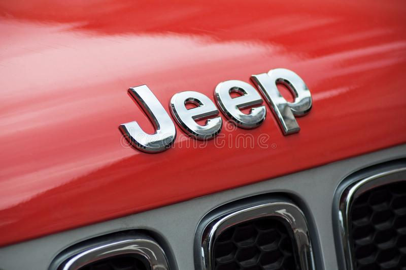 O close up do logotipo do jipe no carro dianteiro alaranjado estacionou na rua fotografia de stock royalty free