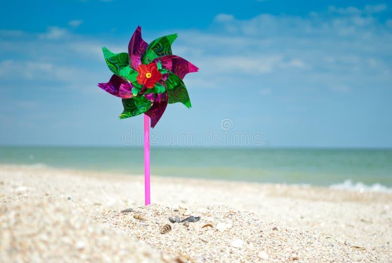 O close-up do moinho de vento do brinquedo no fundo da areia do mar e do céu, brinquedo do jogo das crianças coloriu a aleta de t imagem de stock royalty free