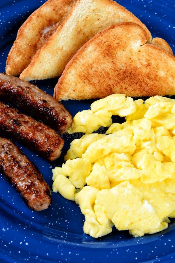 O close up do ovos mexidos toma o pequeno almoço com brinde e três relações da salsicha fotografia de stock royalty free