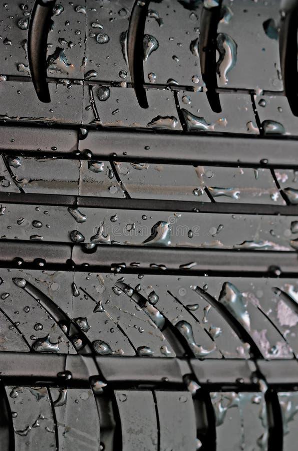 O Close-up do pneu de carro com com água deixa cair