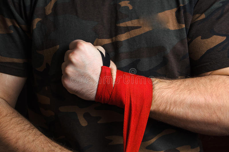 O close-up do pugilista da mão puxa envoltórios do pulso antes da luta foto de stock