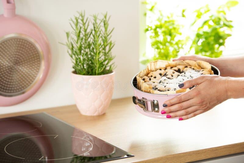 O close-up do ` s da menina entrega guardar um formulário do cozimento com um bolo acima de uma bancada em uma cozinha fotos de stock