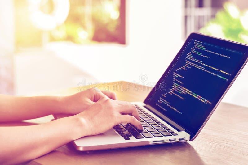 O close-up do ` s do programador entrega o trabalho em códigos fonte sobre um portátil fora foto de stock royalty free