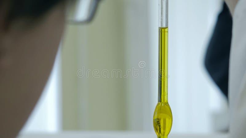O close-up do tubo de vidro com líquido azul na mão do cientista durante cientistas do exame médico entrega guardar um tubo de en fotos de stock
