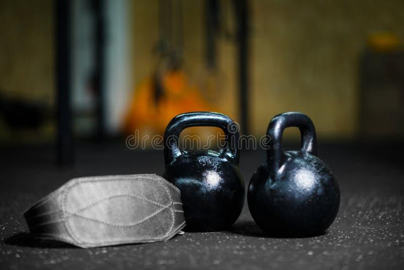 O close up dos kettlebells de aço pretos usados para executar exercícios balísticos, correia atlética cinzenta em uma obscuridade foto de stock royalty free