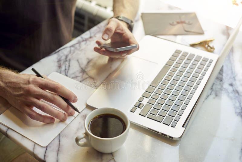O close-up dos man's entrega usando o smartphone, fazendo anotações, portátil aberto que senta-se no café que come o café Conce fotografia de stock royalty free
