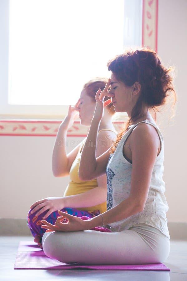O close up dos pares de mulheres na ioga classifica a respiração dos exercícios técnica imagens de stock
