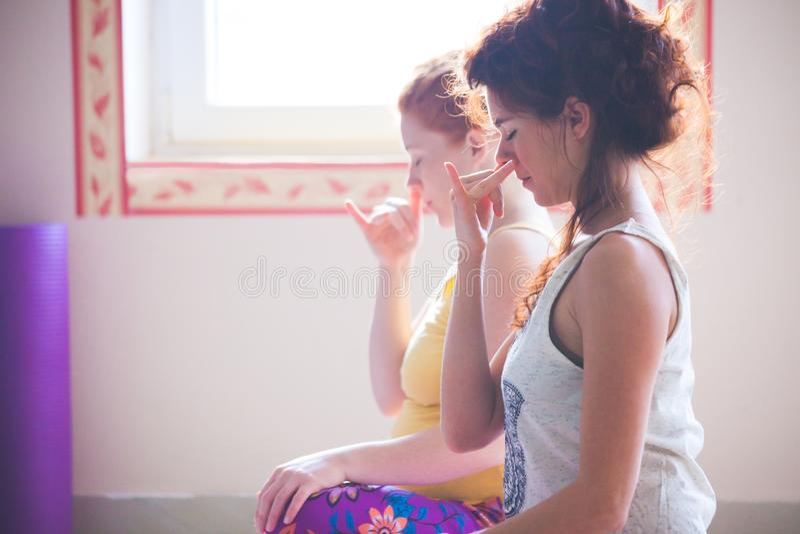 O close up dos pares de mulheres na ioga classifica a respiração dos exercícios técnica foto de stock