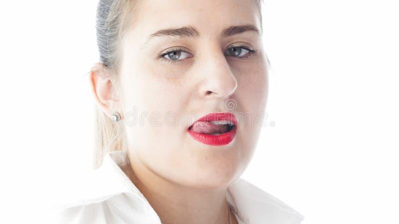O close up isolou o retrato da jovem mulher 'sexy' com batom vermelho que lambe seus bordos com língua imagens de stock