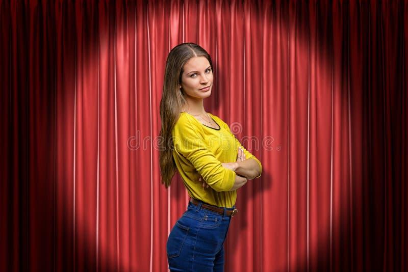 O close-up lateral da jovem mulher na ligação em ponte amarela e da calças de ganga iluminou-se acima pela posição do centro das  fotografia de stock