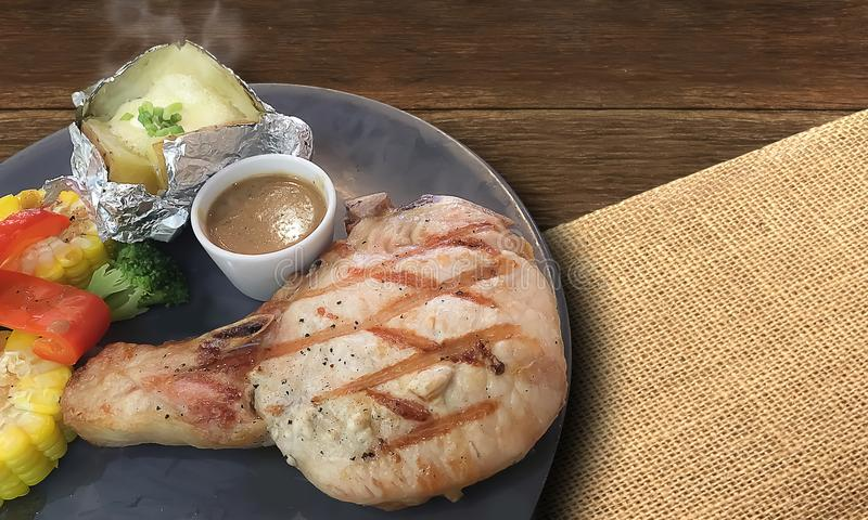 O close up no bife de costeleta da carne de porco Grilled com a batata fresca quente coze imagens de stock royalty free