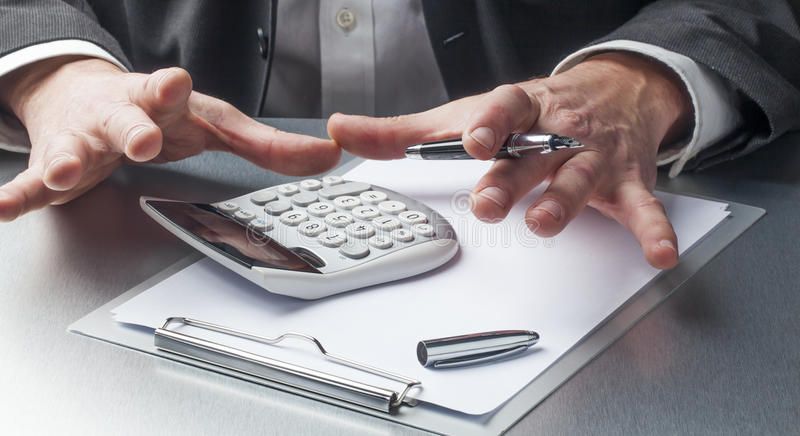 O close up no homem de negócios entrega a indicação da calculadora e das notas para o conceito financeiro fotografia de stock royalty free
