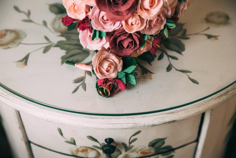 O close-up os anéis de ouro dos recém-casados e o boutonniere do ` s do noivo encontra-se em uma tabela de madeira do vintage Um  fotos de stock royalty free