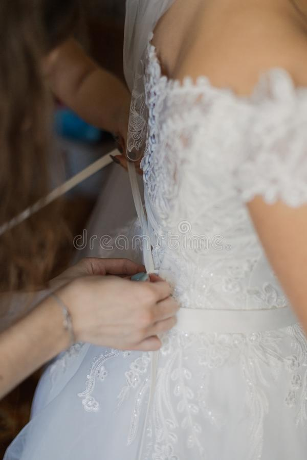 O close up tonificou a foto da noiva bonita que amarra acima de seu vestido de casamento fotos de stock royalty free