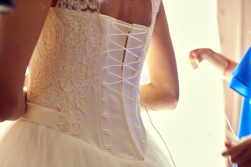 O close up tonificou a foto da noiva bonita que amarra acima de seu vestido de casamento imagem de stock royalty free