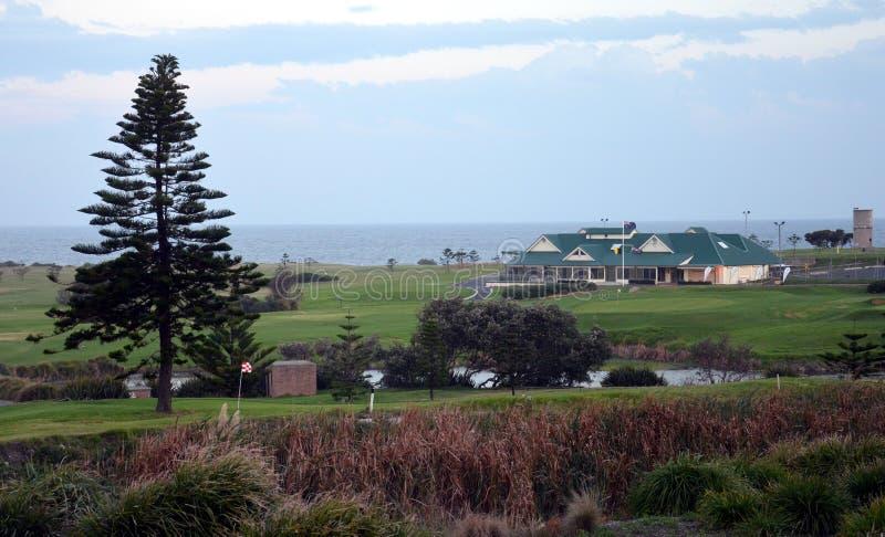 O clube e o campo de golfe de golfe da costa em pouca baía no por do sol foto de stock royalty free