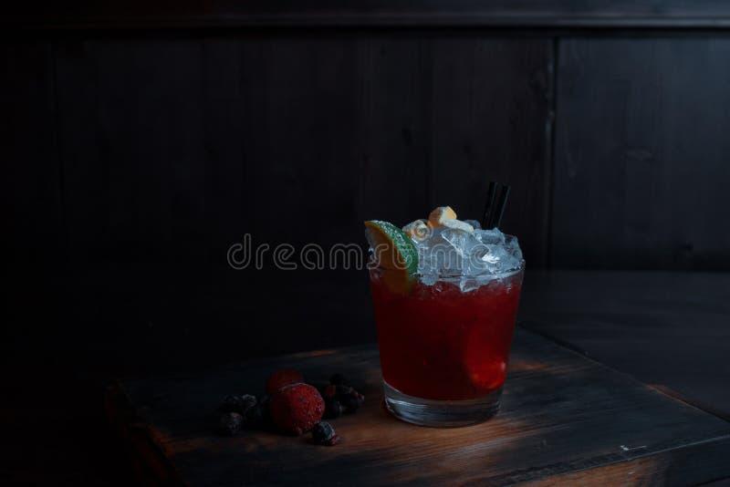 O cocktail alcoólico vermelho doce saboroso com xarope do gelo e da cereja com vodca em um cristal está em uma tabela de madeira  fotos de stock