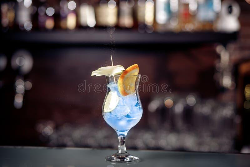 O cocktail azul do verão está na barra com laranja e cal imagens de stock royalty free