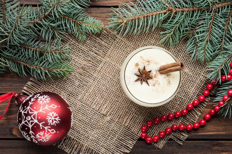 O cocktail da gemada no vidro arranjou com a decoração do Natal em w foto de stock