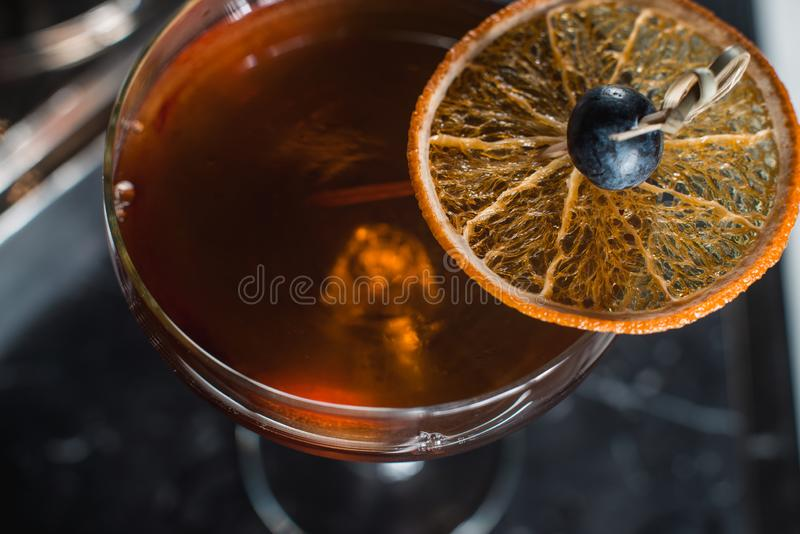 O cocktail de Boulevardier com as microplaquetas alaranjadas na parte superior Em uma mesa da barra fotos de stock royalty free