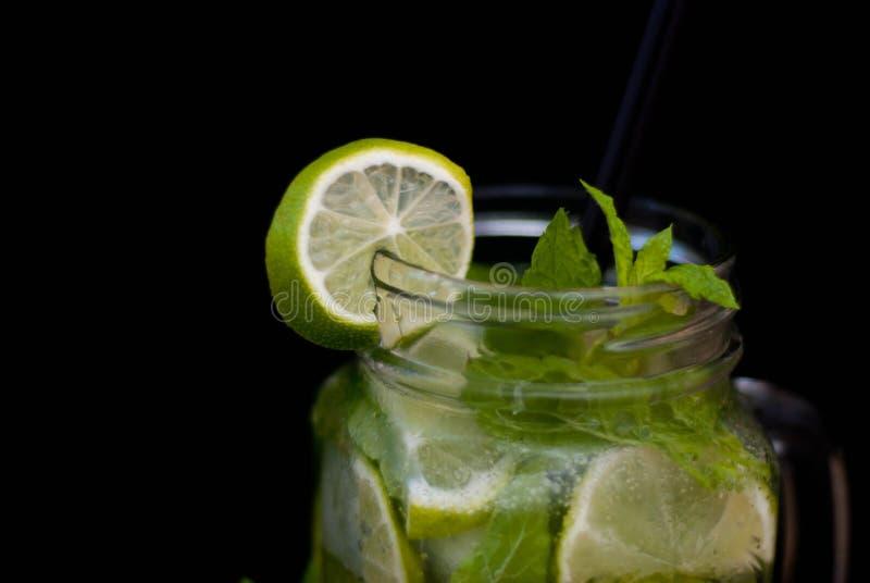 O cocktail do verão de Mojito na água preta do fundo deixa cair as folhas de hortelã dos citrinos do cal imagens de stock