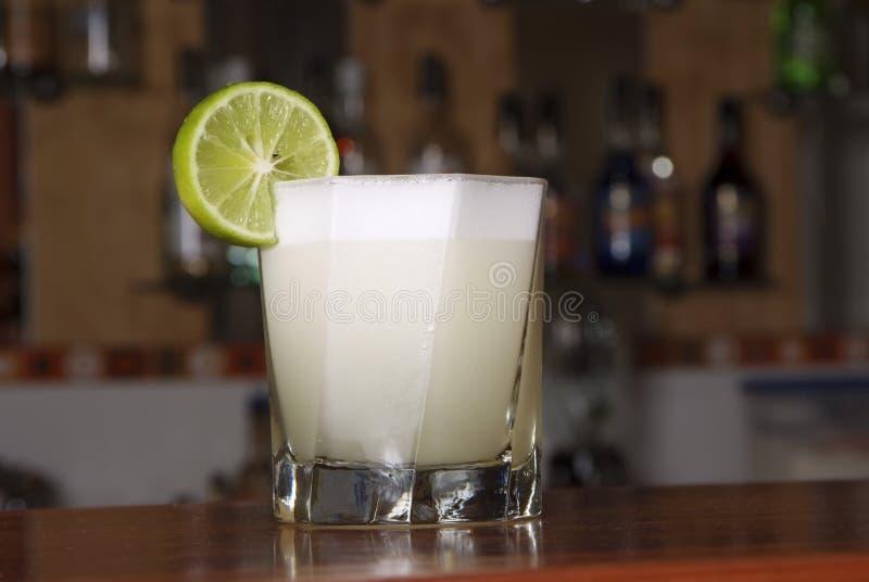 O cocktail peruano chamou ácido de Pisco feito da aguardente da uva de Pisco, do suco de lima, do xarope, da clara de ovos, e de  foto de stock
