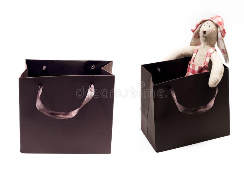O coelho do brinquedo em um chapéu senta-se em um saco emrty do presente de ana do pacote do marrom do presente isolado fotos de stock