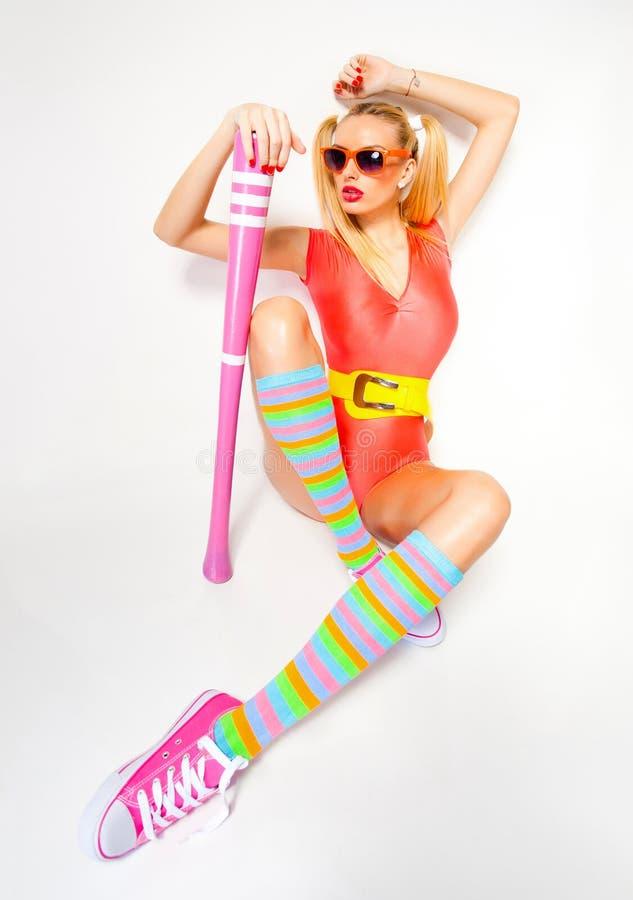 O colorfull vestindo da menina 'sexy' do basebol veste o levantamento com um bastão de beisebol fotografia de stock royalty free