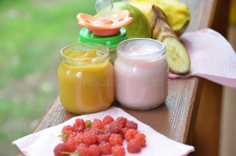 O comida para bebê no puré dos frascos triturou o alimento em um fundo da folha, com uma banana da pera, a chupeta e uma colher foto de stock