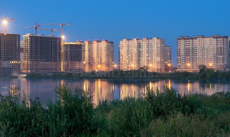 O complexo residencial novo sob a construção no banco do marítimo-fluvial à luz das luzes da noite refletiu na água com imagem de stock