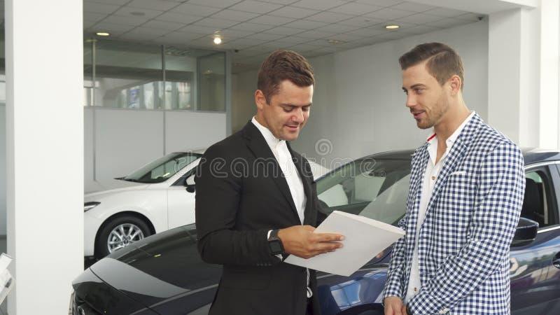 O comprador e o vendedor potenciais leram as características do carro fotos de stock royalty free