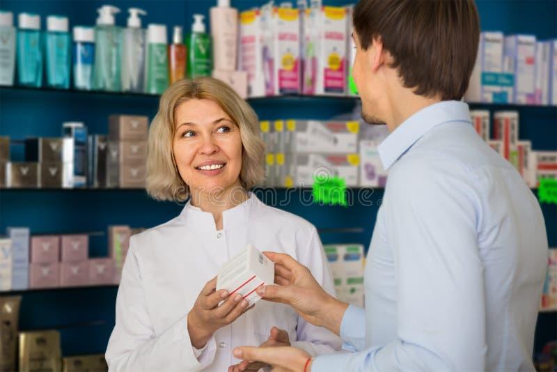 O comprador masculino consulta com o farmacêutico foto de stock