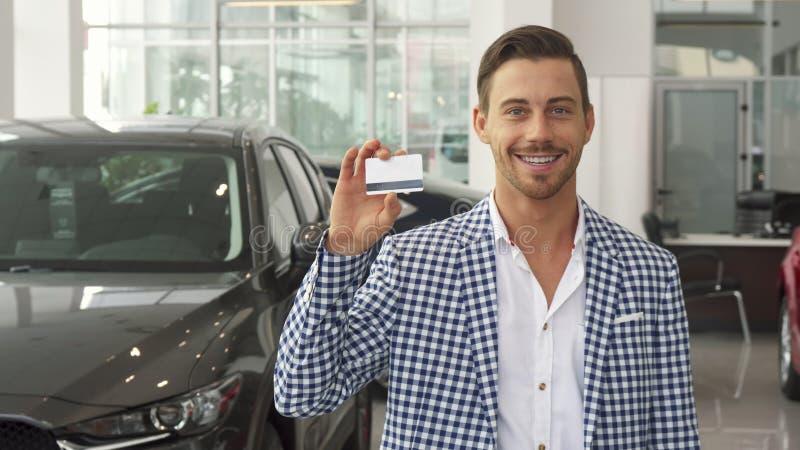 O comprador novo feliz do carro mostra seu cartão de crédito imagens de stock