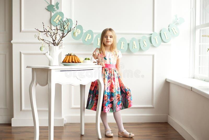 O comprimento completo de uma menina de sorriso pequena no vestido colorido que levanta em uma sala decorada para a Páscoa do fer fotos de stock