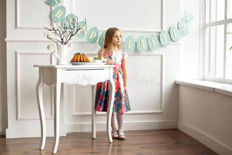 O comprimento completo de uma menina de sorriso pequena no vestido colorido que levanta em uma sala decorada para a Páscoa do fer foto de stock