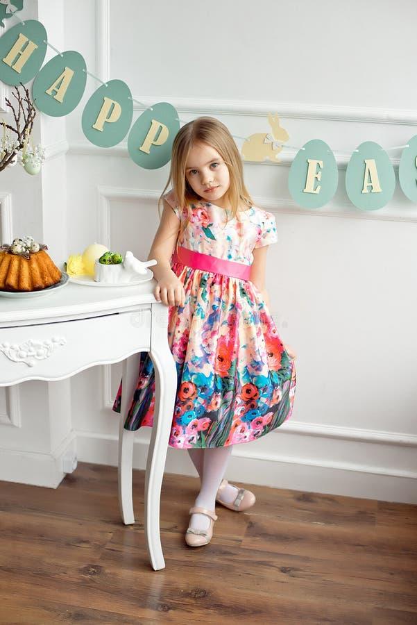 O comprimento completo de uma menina de sorriso pequena no vestido colorido que levanta em uma sala decorada para a Páscoa do fer fotografia de stock