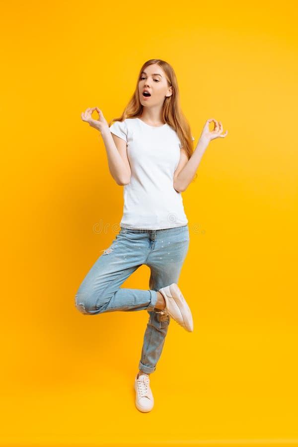 O comprimento completo, menina alegre está meditando em um bom humor, em um fundo amarelo imagens de stock royalty free