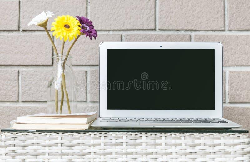 O computador do close up na madeira borrada tece a tabela e o fundo marrom da textura da parede de tijolo, interior bonito do lug fotografia de stock