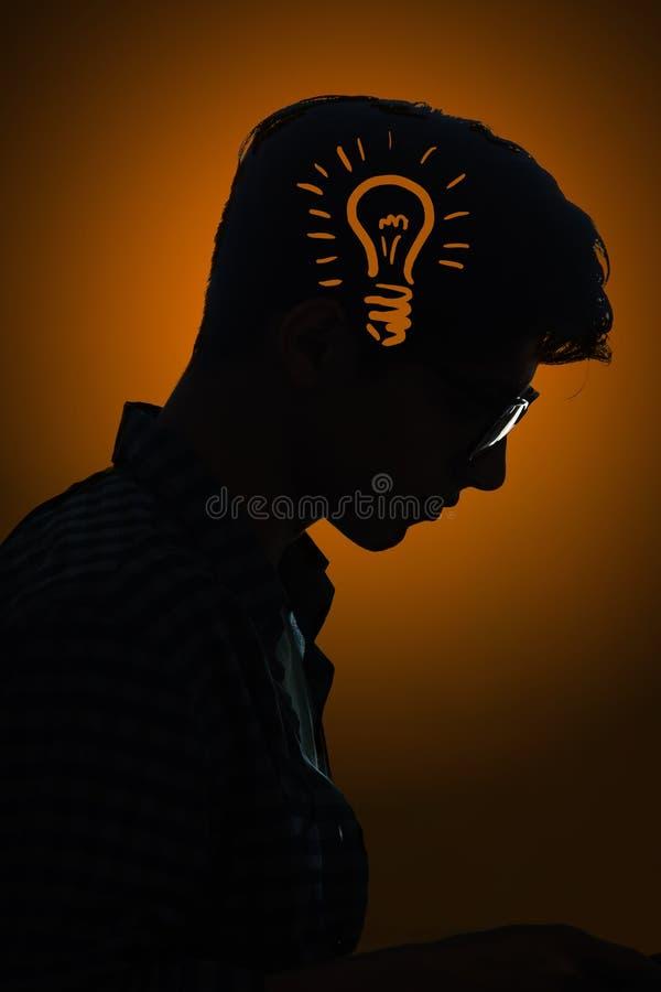 O conceito brilhante da ideia com ampola e homem imagens de stock