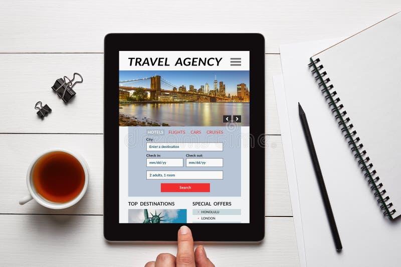 O conceito da agência de viagens na tela da tabuleta com escritório objeta foto de stock