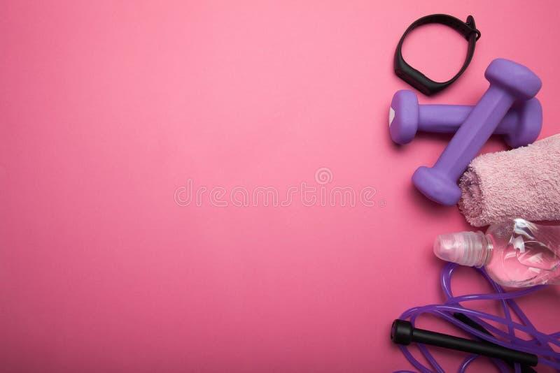 O conceito da aptid?o - pesos, corda de salto, bracelete da aptid?o, fones de ouvido e ?gua Fundo cor-de-rosa Copie o espa?o para imagens de stock