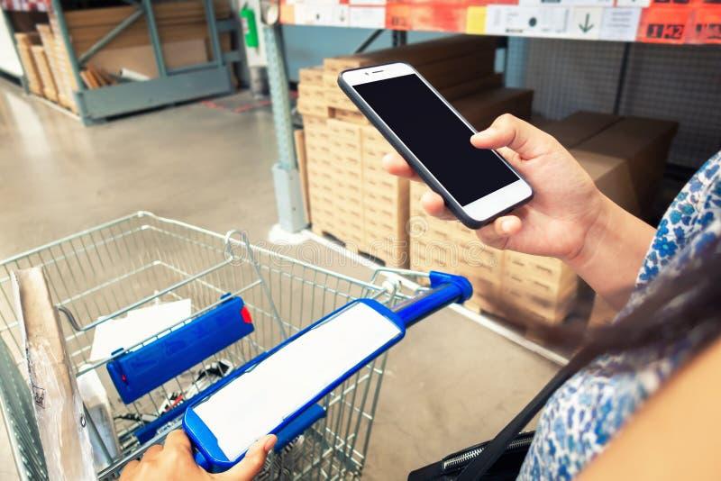 O conceito da compra da consumição e da comunicação da tecnologia, mão da mulher do close-up está usando o telefone celular quand imagem de stock