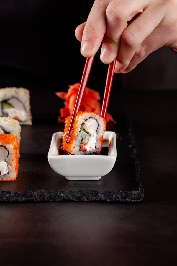 O conceito da culinária japonesa Uma menina guarda hashis chineses vermelhos e come o sushi em um restaurante Imagem de fundo pop foto de stock