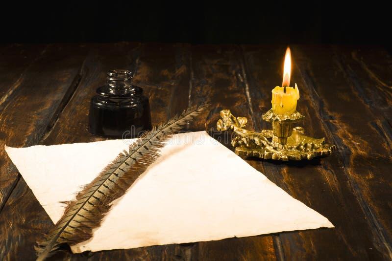 O conceito da educação e da escrita, a pena na garrafa de tinta e a vela guardam imagens de stock royalty free