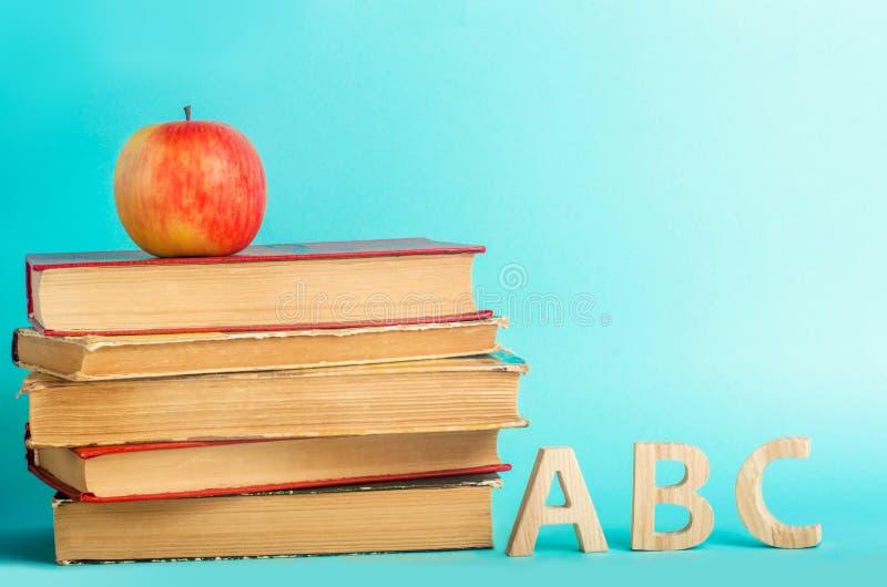 O conceito da educação maçã, livros e alphabe, fundo azul, lugar para o texto, de volta à escola, espaço da cópia foto de stock