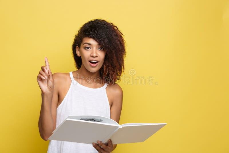 O conceito da educação - retrato da mulher afro-americano que lê um livro e obtém algumas ideias Fundo amarelo do estúdio cópia imagens de stock royalty free