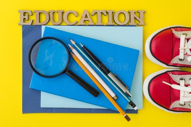 O conceito da educação Sapatilhas vermelhas, fontes de escola, livros, cadernos com fundo amarelo imagem de stock royalty free
