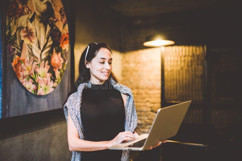 O conceito da empresa de pequeno porte e da tecnologia Mulher de negócios moreno bonita nova no vestido preto e em suportes cinze fotos de stock royalty free